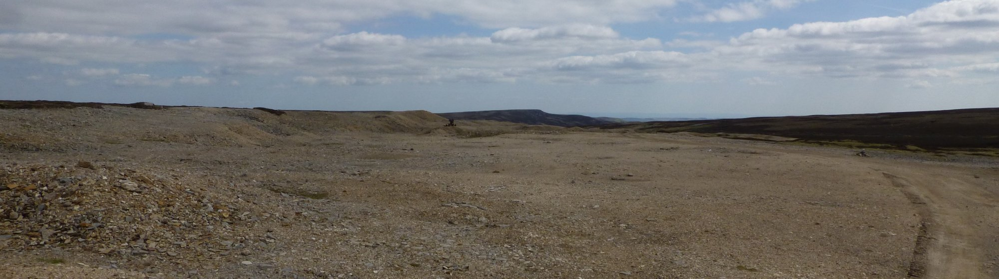 Stone crusher sits in the vast moonscape of spoil heaps