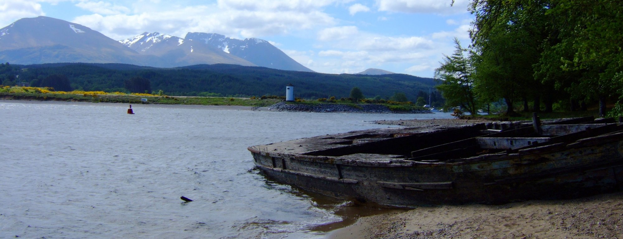 From left to right Aonach Mor, Carn Mor Dearg and Ben Nevis, above the pepperpot lighthouse and ruined barge at Gairlochy