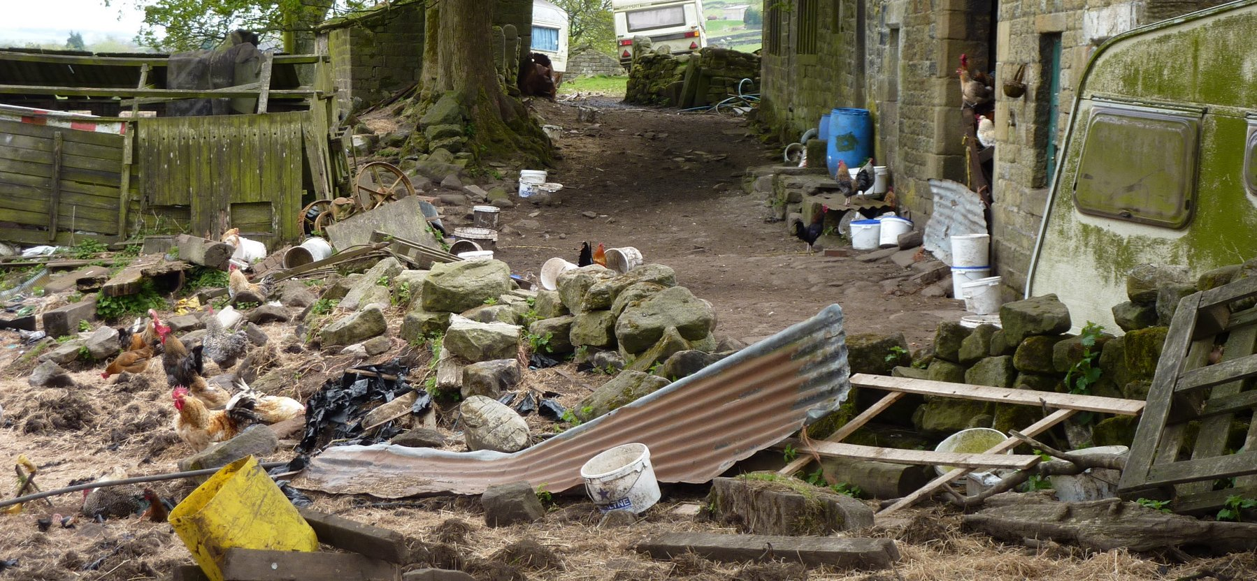 Shameful, litter-strewn yard of a farm on the descent to Ponden