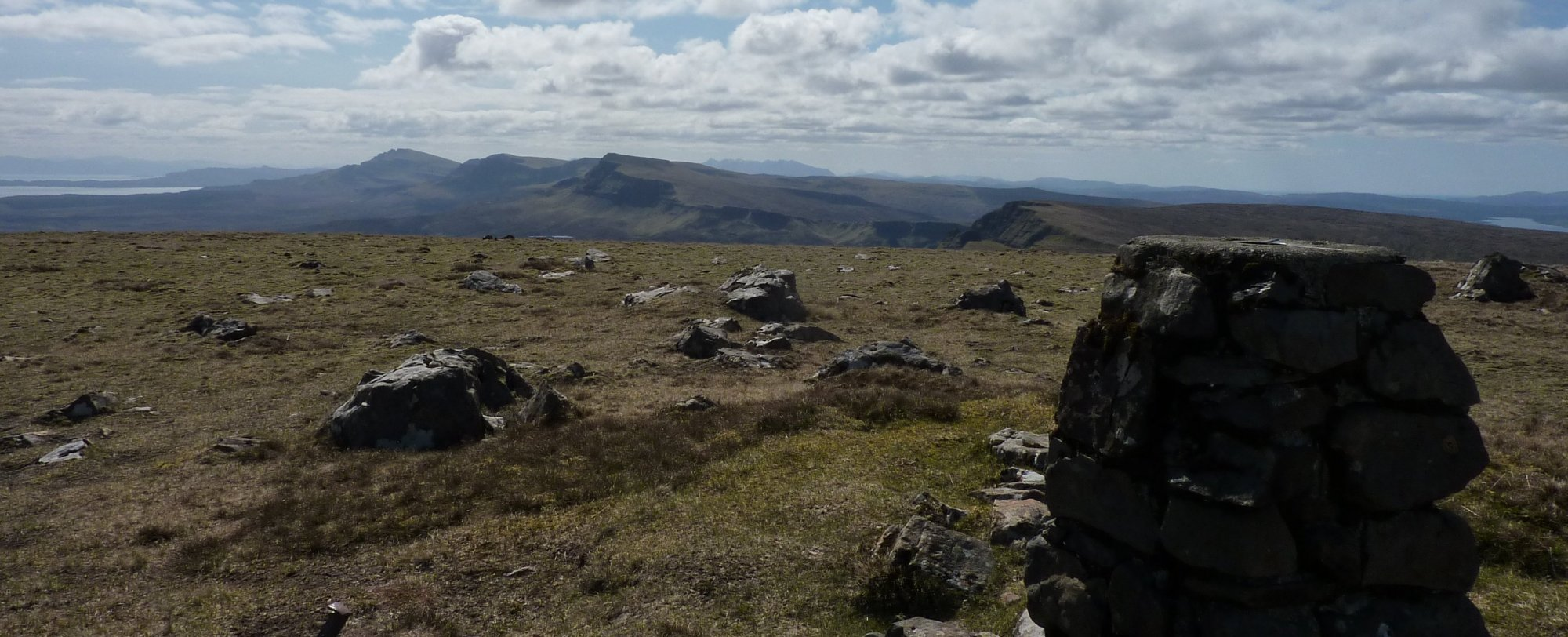 The Trotternish ridge and the distant Cuillins behind the trig point on Meall na Suiramach