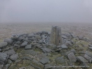 The bitterly cold summit of Cross Fell, with frost on the trig point