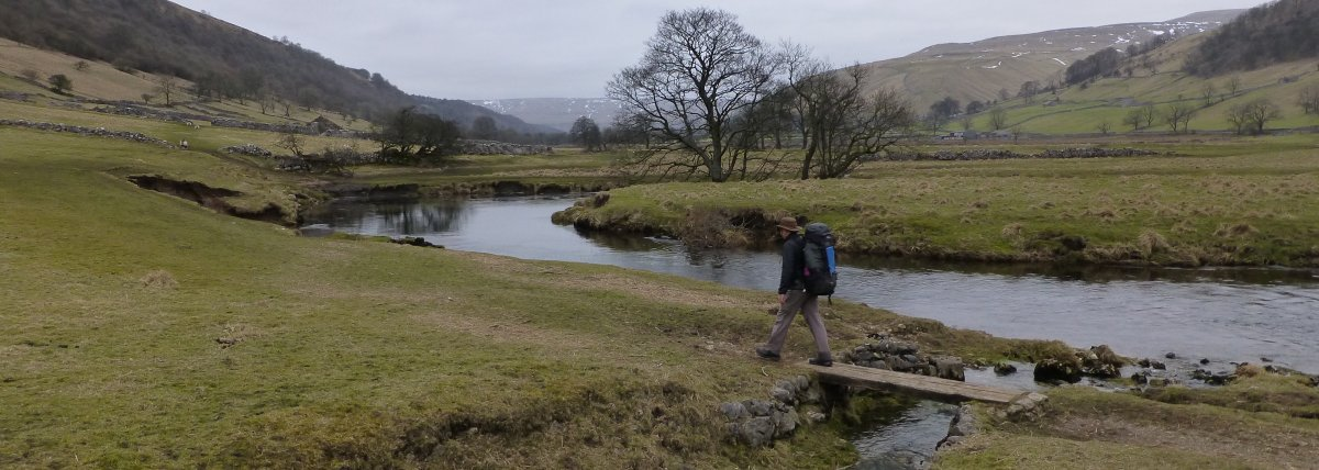 Chris crosses a little bridge on the Dales Way path beside the Wharfe