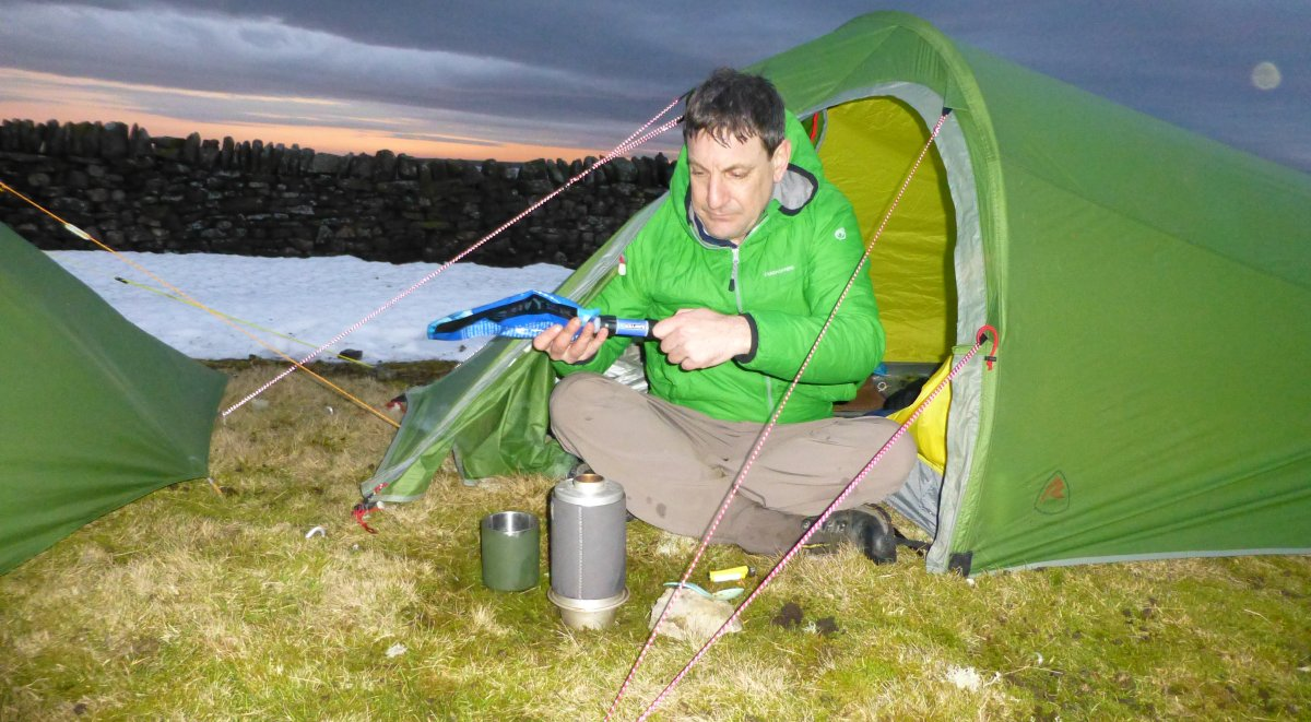 Chris, preparing tea with the sun going down over the Lake District