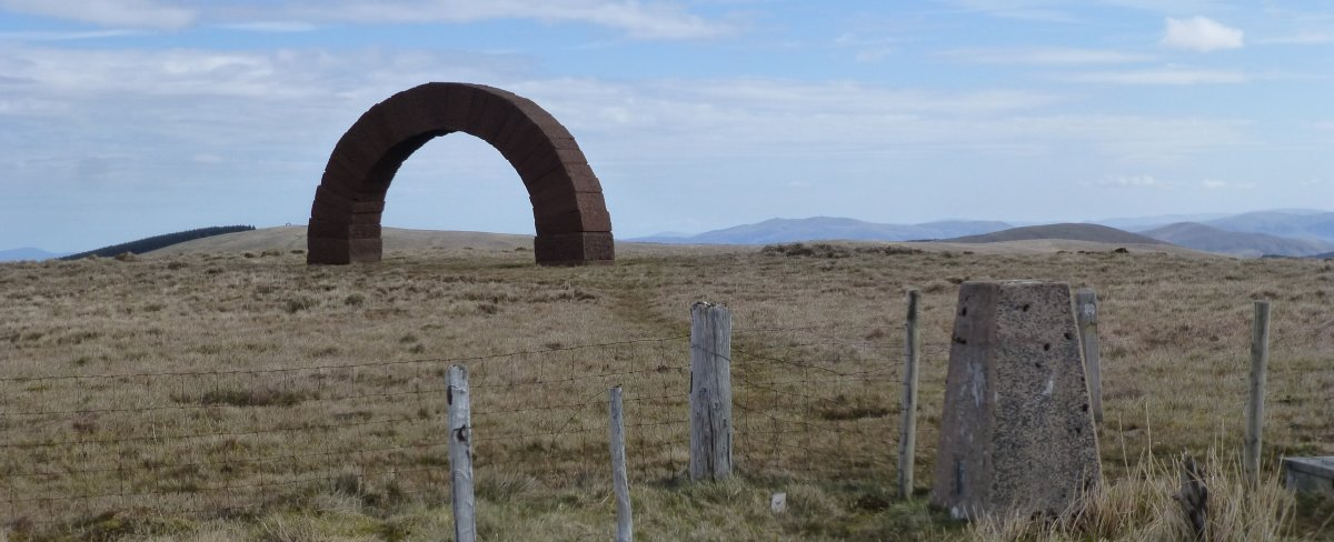 Trig point and sanstone arch on summit of Benbrack